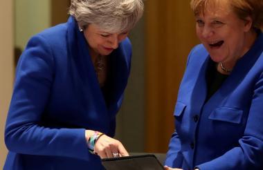 Theresa May y Angela Merkel en medio de reunión.