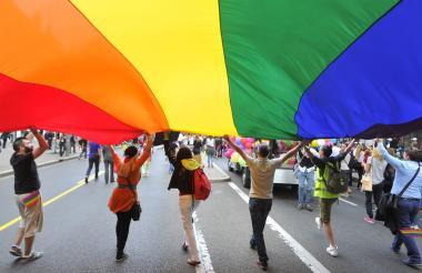 Personas de diferente orientación sexual sostienen  bandera del Orgullo Lgbtiq.