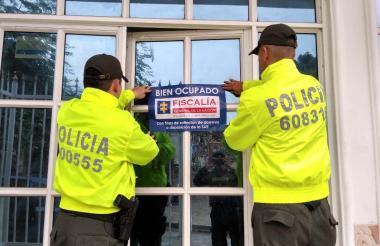 Uniformados pegan un cartel en uno de los inmuebles.