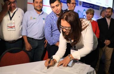 Diana León firma el acta. La observa el ministro Malagón y otros funcionarios.