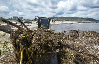 Uno de los cargadores remueve basuras de la orilla de una de las playas de Puerto Colombia.