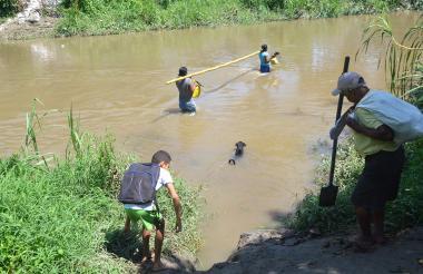Habitantes atraviesan el río