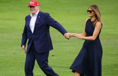 El presidente Trump y la primera dama Melania Trump caminan por los jardines de la Casa Blanca.