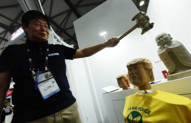 Un visitante prueba el juego estrella en China: golpea la cabeza de un maniquí que tiene la imagen de Donald Trump.