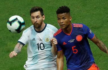 Messi y Barrios disputando el balón.