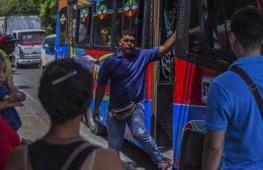 Leonardo Gutiérrez, ayudante de bus hace dos años, vocifera la ruta del vehículo ante los pasajeros que esperan en Santo Tomás.