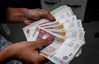 Una persona cuenta billetes de baja denominación.
