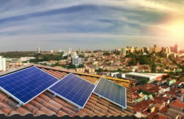 Equipo de paneles solares ubicados sobre el techo de una vivienda, en una zona urbana, para autogeneración de energía.
