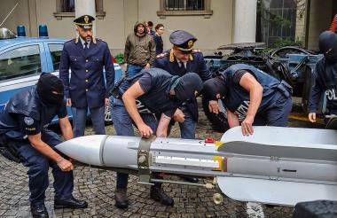 Policía italiana sostiene misil aire- aire incautado.