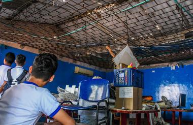 Aspecto del interior del aula con el techo caído y los escritorios deteriorados.