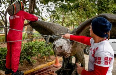 Dos técnicos realizan las labores de limpieza del águila, en la Aduana.