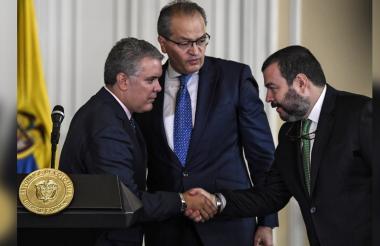 El presidente Ivan Duque y el defensor del pueblo Carlos Alfonso Negret, junto al procurador general general Fernando Carrillo, durante la firma de un decreto.