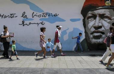 Un grupo de personas pasan por un grafiti con la imagen de Hugo Chávez.