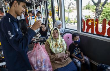 Conductor de autobús recoge botellas de plástico usadas como pago de tarifa a bordo de un autobús.