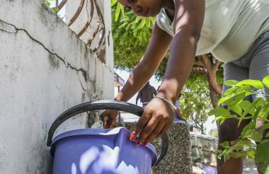 Una habitante recicla agua en un balde.