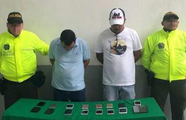 Los dos capturados con parte de los celulares que les fueron incautados.