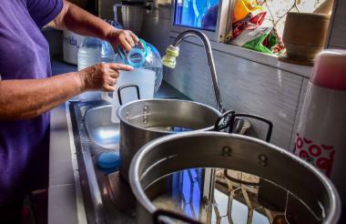 Una de las vecinas del barrio Buenos Aires recolecta agua por precaución ante las fallas.