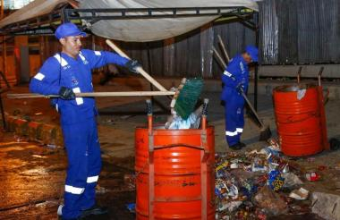Dos operarios de Triple A recogen basuras en una calle de Barranquilla, luego de un evento de Carnaval.