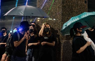 Manifestantes apuntan con rayos láser a un edificio del gobierno en la protesta.