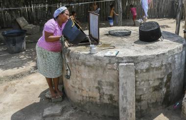 Una habitante de Leña  recoge agua que recolecta en una alberca de su vivienda.