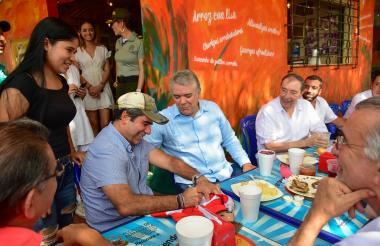 El presidente Duque saluda a una hincha del Junior mientras el alcalde Char firma una camiseta.