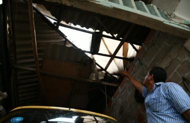 Un residente de Malambo muestra el daño ocasionado en el techo por las fuertes brisas.