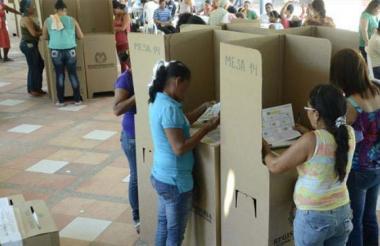 Ciudadanos sostienen tarjetón de candidatos para ejercer su derecho al voto en pasadas elecciones.