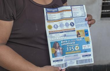 Una usuaria de Los Jobos, barrio de estrato 4, muestra la factura de energía de su domicilio.