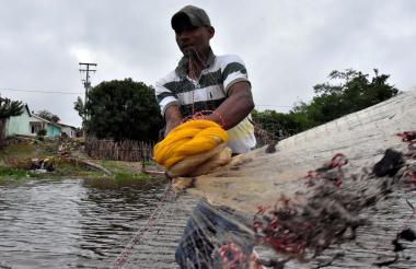 Un pescador se prepara para lanzar su atarraya en un caño del municipio de Ponedera. Atrás se ve un tubo descargando aguas servidas.