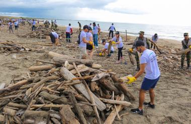 Personal realizando labores de limpieza en playa.