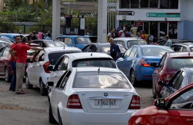 Conductores hacen fila en una estación de gasolina.