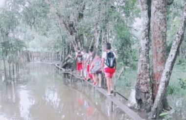 Estudiantes caminan sobre un puente artesanal en una de las zonas afectadas de Sucre.