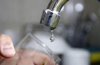 Una persona recoge agua en un vaso.