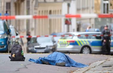 Un cuerpo tendido en la calle está cubierto mientras la policía bloquea el área alrededor del sitio de un tiroteo en Halle, Alemania.