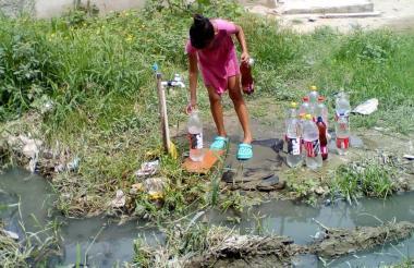 Habitante del barrio recogiendo agua en botellas porque no tienen acueducto.
