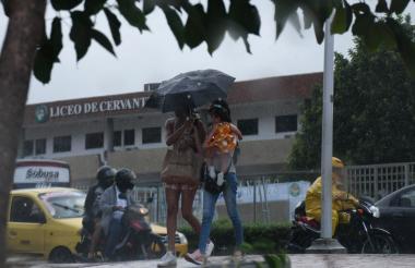 Dos mujeres con bebé en brazo se resguardan de la lluvia con su paraguas.
