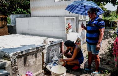 Leidys Mauri y su mamá instalan una nueva lápida a la tumba de su tía.