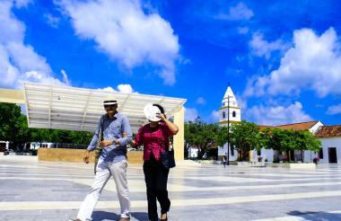 Una pareja camina al mediodía en la Plaza Alfonso López. Lo hacen protegiéndose la cabeza y los ojos por el resplandor que produce el mármol del piso.