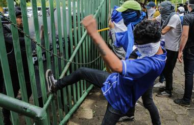 Estudiantes nicaragüenses golpean una barrera.