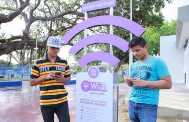 Dos jóvenes aprovechan el WiFi gratis que se ofrece en uno de los parques de Barranquilla.