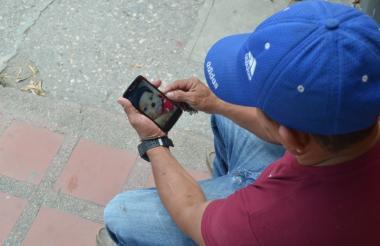 Uno de los abuelos observa en su teléfono celular la imagen de su nieta de 17 meses, fallecida por accidente casero.