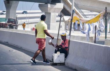 Vendedor ofreciendo toallas y bebidas refrescantes.