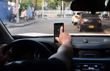 Un conductor de aplicaciones de transporte compartido selecciona un servicio en su teléfono inteligente.