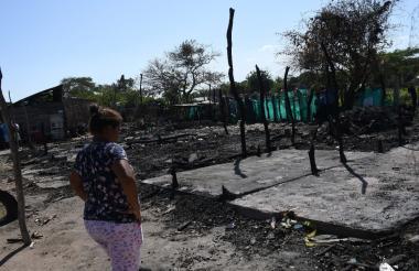 Una mujer mira con nostalgia el lugar donde solía estar su casa, calcinada por el incendio.
