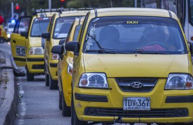Varios taxis se movilizan por una vía en el centro de Barranquilla.