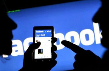 Dos personas interactúan con la aplicación de Facebook en su celular.