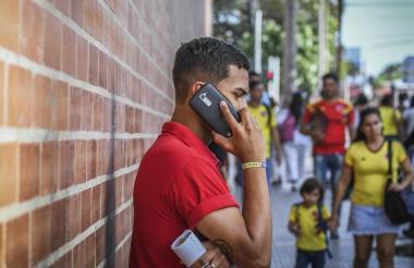 Un joven habla por su teléfono celular.
