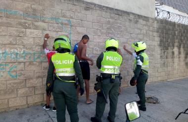 Policías requisan a un grupo de personas durante la cuarentena.