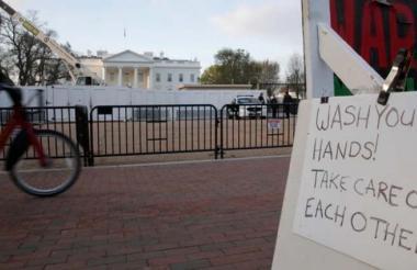 """Un cartel recuerda a la gente que se """"lave las manos """" frente a la Casa Blanca en Washington, EEUU."""