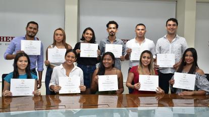 Los 11 estudiantes que se graduaron del curso enseñan sus diplomas.
